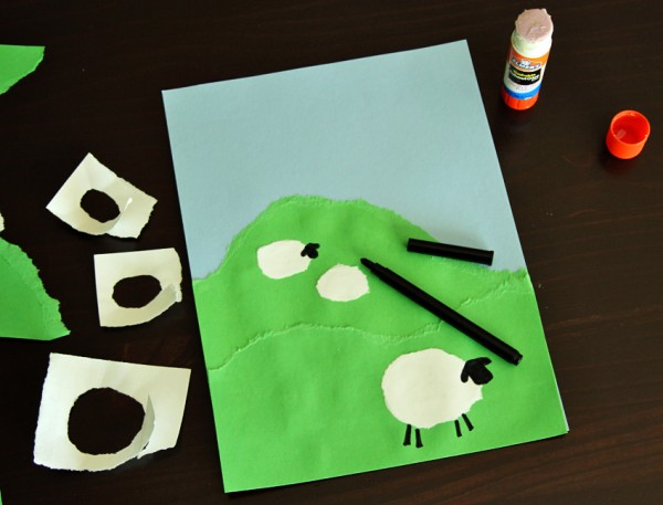 Torn paper sheep on a hill