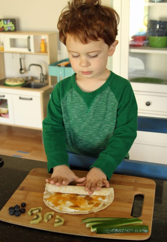 Rolling a cream cheese and jelly tortilla