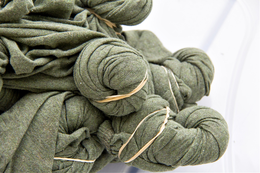 green sheets twisted and tied with rubber bands for dyeing with bleach